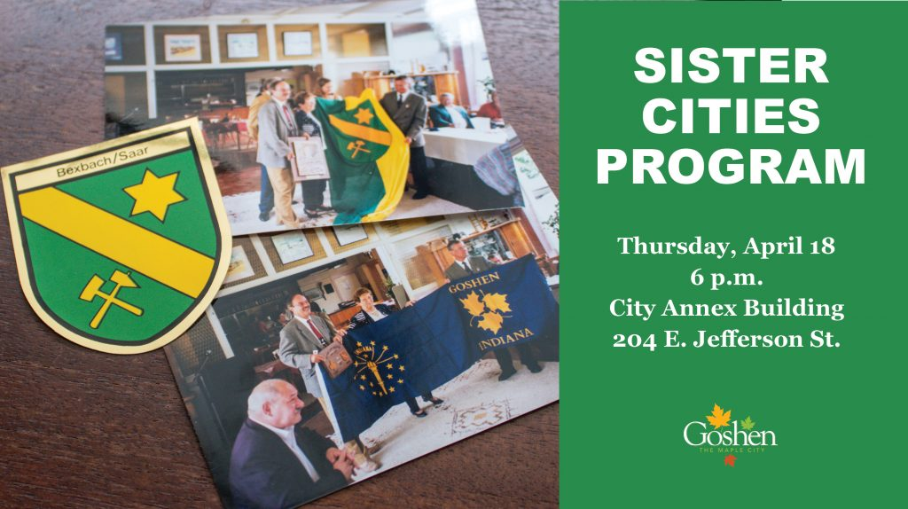 "Bexbach coat of arms and two photos of people with flags of Bexbach and Goshen. Text on right says: ""Sister Cities Program, Thursday, April 18, 6 p.m., City Annex Building, 204 E. Jefferson St."""