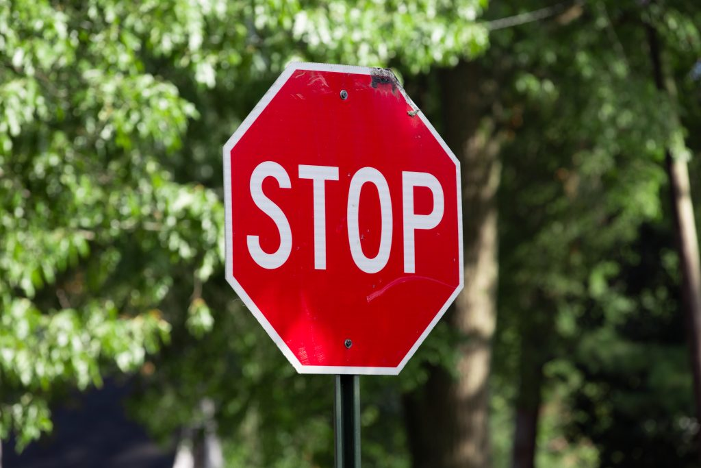Red stop sign with green tree background.