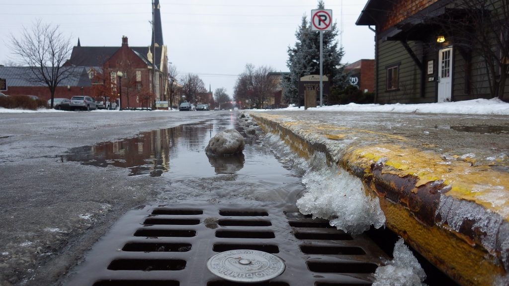 Up close look of a storm drain, snow and pooled water in the background