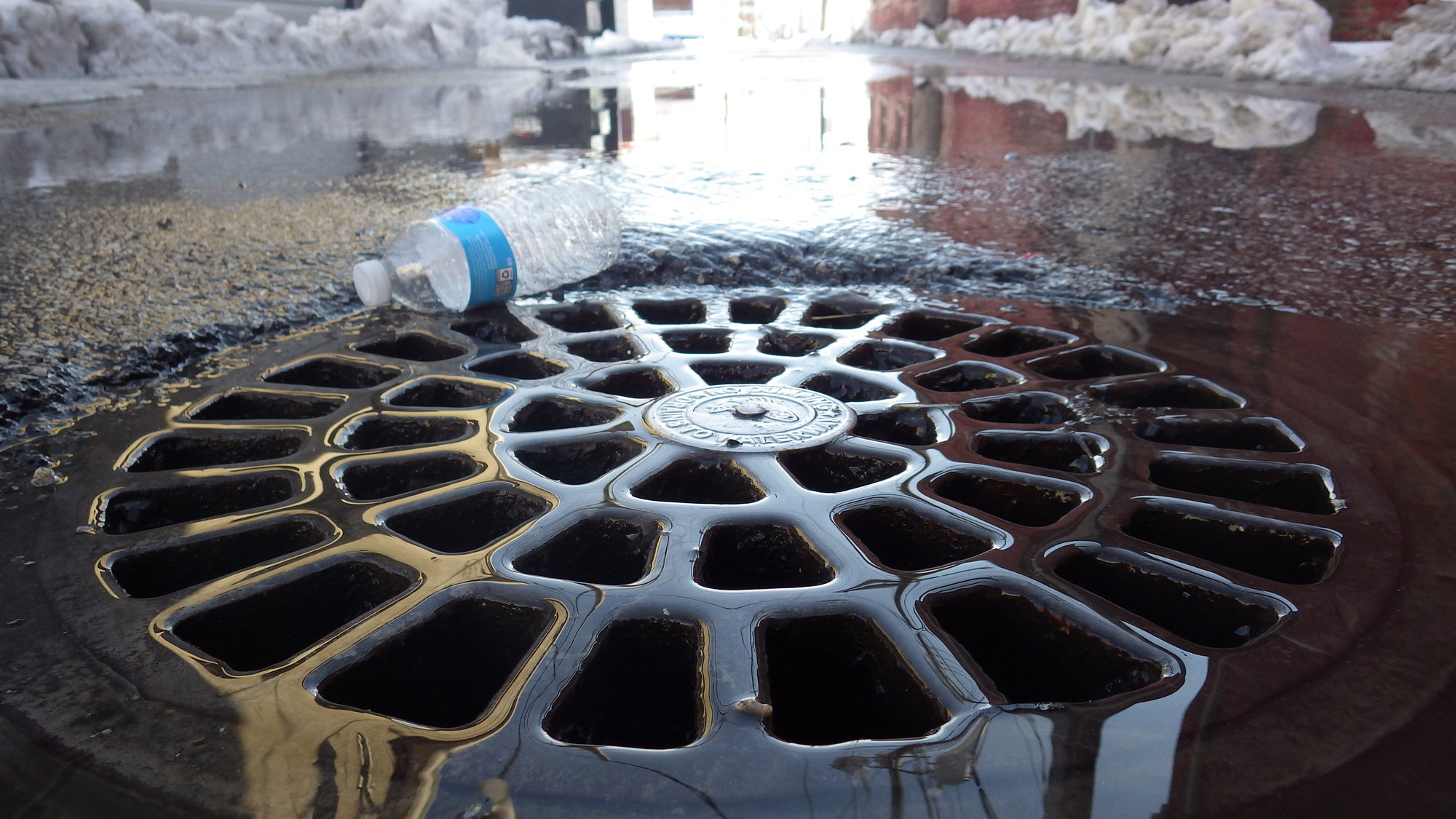 Stormwater runoff from snomelt running into a storm drain.