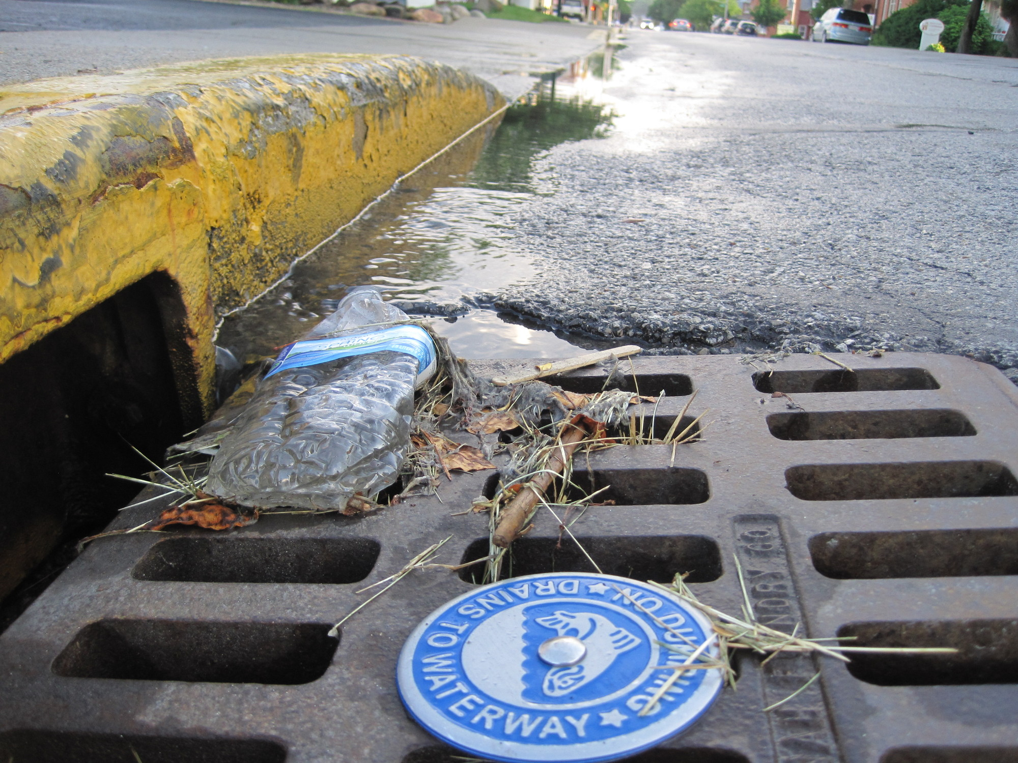 Over time trash, grass clippings, and sediment can accumulate around a storm drain inlet and cause drainage issues.