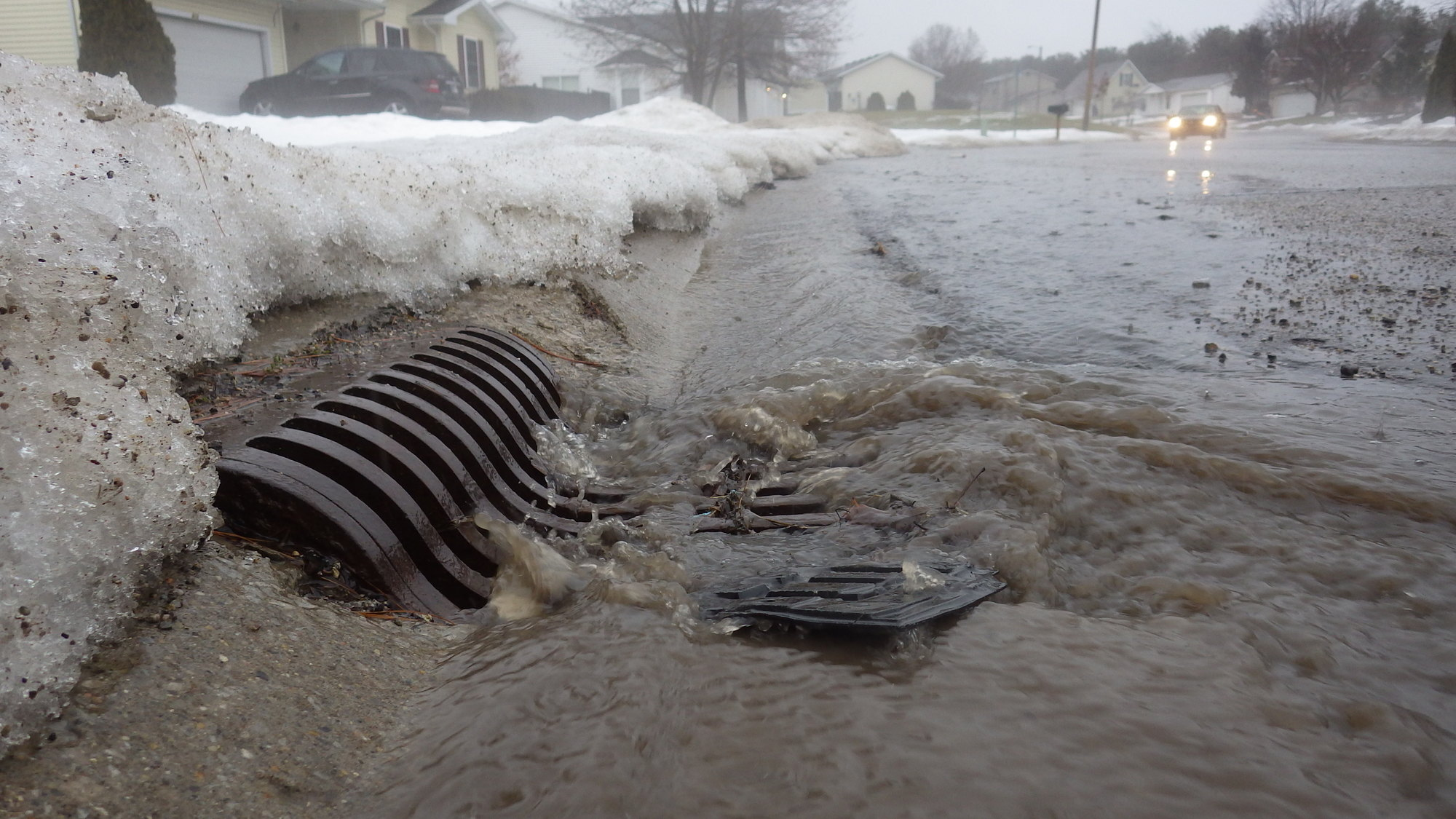 Stormwater runoff from snomelt and a rainstorm running into a storm drain.